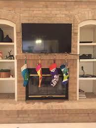 tv on brick above a fireplace