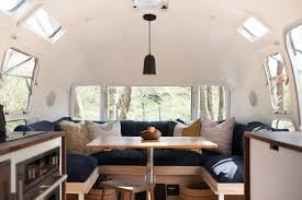 The dining area of Modern Caravan's vintage Airstream features a custom  table made from salvaged boards