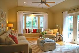 warm living room ideas: pastel color scheme living room design with window bay sofa and pillows green pastel walls