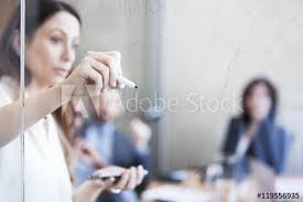 businesswoman writing on glass wall during meeting