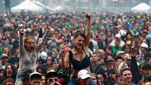members of a crowd numbering tens of thousands smoke and listen to live at the