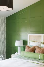 serena lily feather wallpaper complements a green board and batten accent wall positioned behind a french cane headboard supporting a bed dressed in white