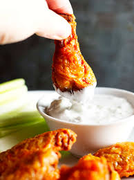 dipping crispy baked buffalo wings in blue cheese dressing
