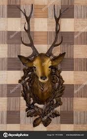plastic deer head mounted imitation wood wallpaper frontal view stock photo