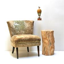 furniture tall round brown tree stump coffee table next to shabby brown fabric chair with