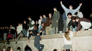 fall of the berlin wall marked end of cold war file east german citizens climb the berlin wall at the brandenburg gate as they celebrate