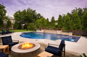 amazing modern pool design black outdoor chairs modern rounded fireplace light flooring beautiful shaped pool natural green plants view