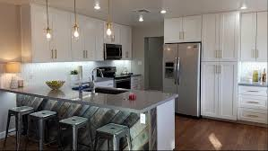this gorgeous kitchen features j k cabinetry s white shaker cabinets with grey quartz countertops the stainless steel appliances are a great contrast to