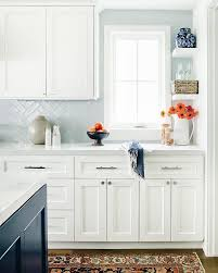 light blue herringbone tiles with white cabinets