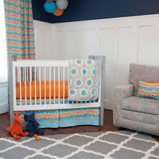 bedroom white wooden cradle with orange bedding plus gray blue blanket placed on the brown