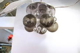 a mid century modern chandelier in chrome and glass comprising of five large smokey
