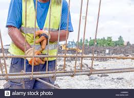 worker is tying rebar to make a newly constructed footing frame binding concrete frame rebar worker