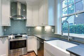 traditional kitchen with white cabinets concerto quartz counters and blue subway tile backsplash