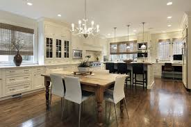spacious white kitchen with eat in peninsula in addition to dining table situated in the spacious eat kitchen