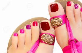 異なる色の塗料緑の背景のピンクのサンダルで女性の足のペディキュアし