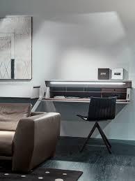 ghostwriter suspended desk leather upholstered sofa decorative artwork dotted black rug dark wooden flooring black chair framed artworks