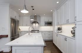 delicate white kitchen cabinets white marble countertops and stainless steel appliances