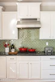 green glass tile backsplash before and after photos of a kitchen that had it s cabinets
