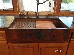 copper farmhouse a sinks with cutting boards and copper drain grids