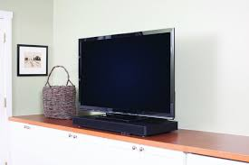 flat screen tv on wall with surround sound. a pedestal-style sound bar, such as this zevox audio soundbase 770, can be placed beneath tv. flat screen tv on wall with surround
