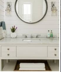 the shiplap covered white walls in the powder room are clic new england coastal style large reen round mirror and sconces from waterworks