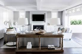 wood barade console table behind a gray sofa in a clic white and gray transitional living room