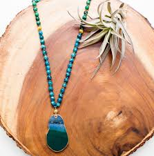 blue agate beaded pendant necklace on wooden stone with plant to right of product