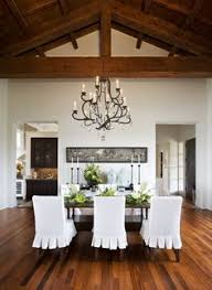 beautiful dining room design with cathedral ceiling iron crystal chandelier wood rectangular dining table white ruffled slip covered dining room chairs