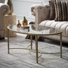 oval glass top coffee table with four dark brown metal legs on grey rug