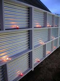 a corrugated metal fence can become realyl cool looking if you place some candles there