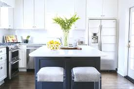 White Kitchen With Gray Island Fitted With Gold Hardware