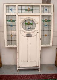 an english front door with oval stained glass panel and stained glass transom and side lights