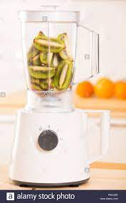 Young man cooking kiwi smoothie in blender Stock Photo - Alamy
