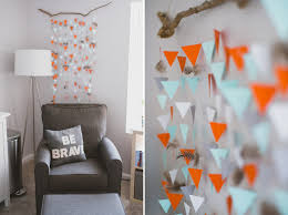 Hanging triangle garland and feather decor in woodland themed nursery