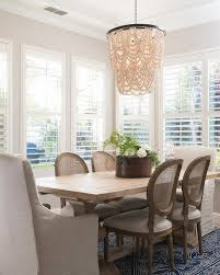 a cream pottery barn amelia chandelier decorates a window framed dining room with a light salvaged wood trestle dining table