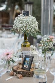 Empty wine bottles were filled with baby's breath and positioned on top of  a wood slab. Candles surrounded the centerpiece on the dining table.
