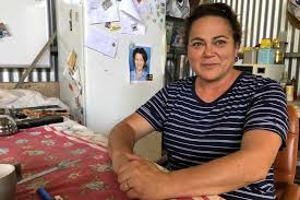 mother sitting on bench with photo of deceased daughter on a fridge behind her
