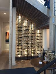 an elegant wine cellar under the stairs with a stone clad wall and metal shelves that