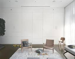 pulltab design white lounge with creative wall storage and heavily textured area rug