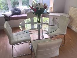 next round glass dining table with four cream white leather chairs