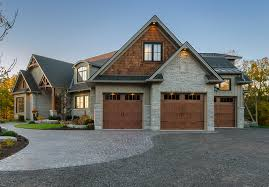 a large home has three elegant wooden garage doors and a sweeping gray stone driveway