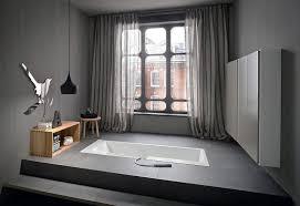 ergonomic sunken bathtub installation by rexa puts bath accessories within reach