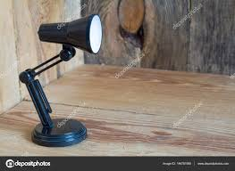 small table lamp made of black plastic on a wooden background stock photo