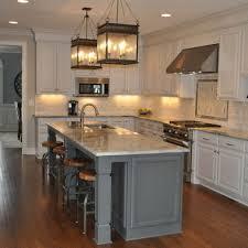 White Cabinets Dark Grey Island Lanterns Above Island Kitchen