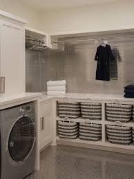 Contemporary laundry room features ivory shaker cabinets paired with white  quartz countertops and mini stainless steel