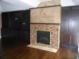 pastel brown and black grey small glass tile mosaic fireplace surround modern black frame and glass ventless gas fireplace living room dark brown laminate
