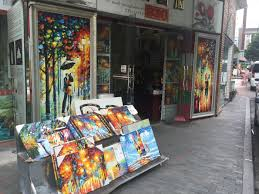 paintings are displayed on a street in china s dafen oil painting village