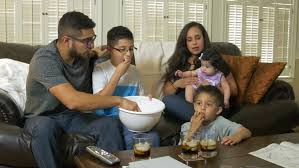 hispanic family watching tv. an attractive hispanic family sitting together enjoying popcorn and television show. - 4k stock video watching tv s