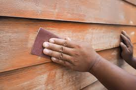 human hands scrubbing wood wall by sandpaper prepare to paint color