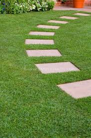 garden paths and stepping stones. stepping stones in perfect lawn grass, leading an arc to backyard patio, with · stone garden pathsstepping paths and